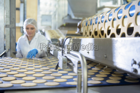 biscuit factory worker inspecting freshly made