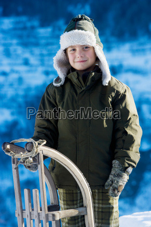 portrait of young boy with sledge