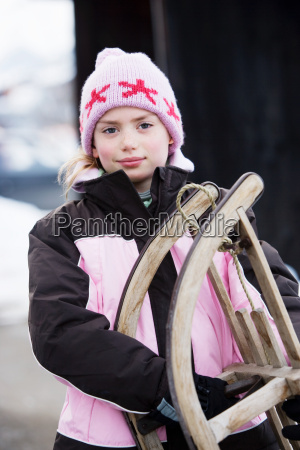 portrait of young girl with sledge