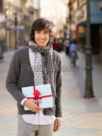 young man standing in street