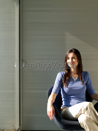 businesswoman sitting in office smiling