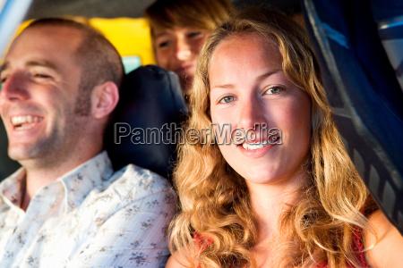 three people in a van smiling