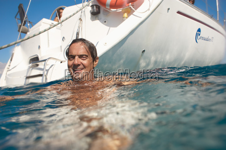 mature man swimming in sea by
