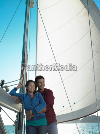 young couple relaxing on yacht smiling