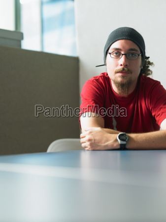 young man sitting at desk portrait