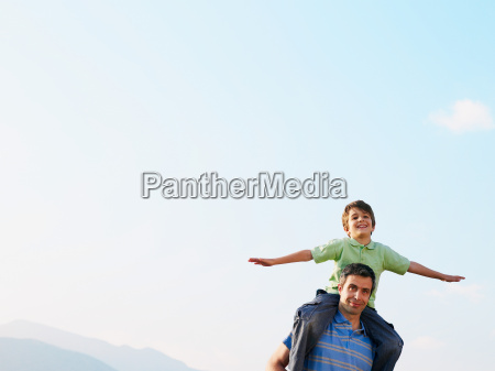 son sitting on fathers shoulders