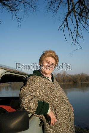 senior woman leaning on car by