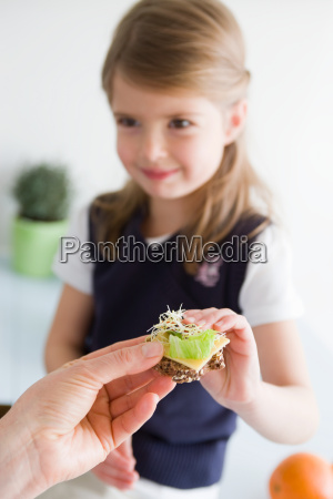 girl taking bread from mother