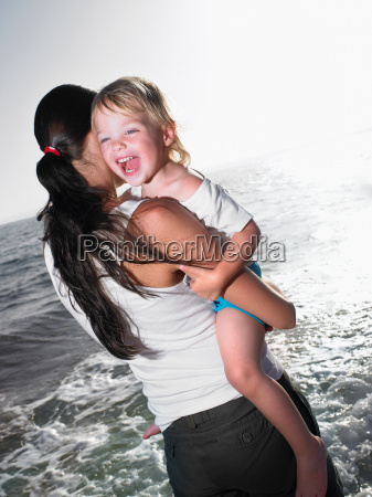 woman holding a smiling young girl