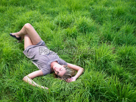 woman relaxing in a green field