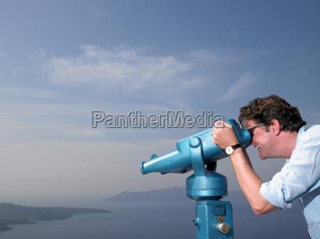 man looking through spyglasses