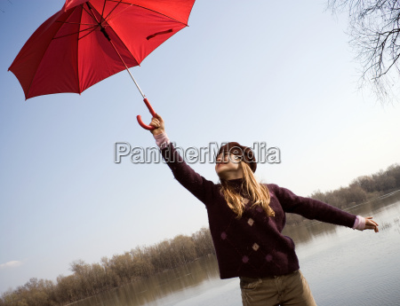 girl by river holding up red