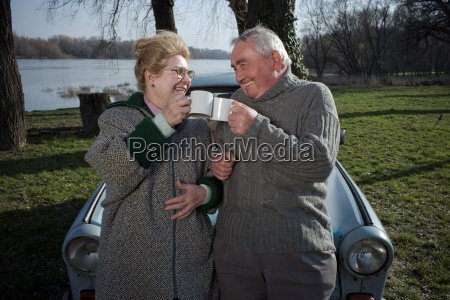 senior couple by car toasting each