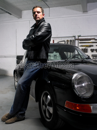 man leaning on a porsche in