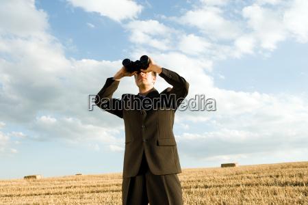 man using binoculars in wheat field