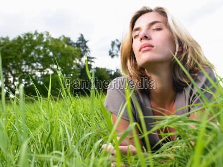 woman relaxing in a green field