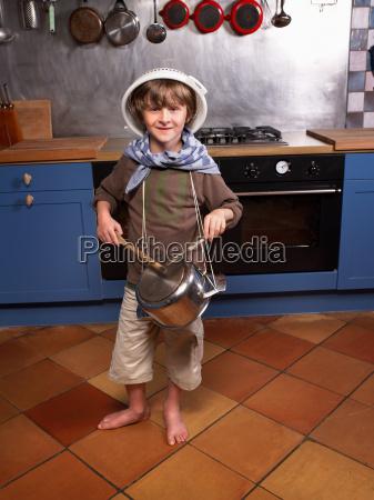 little boy in kitchen drumming