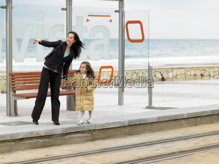 mother and daughter waiting for tram
