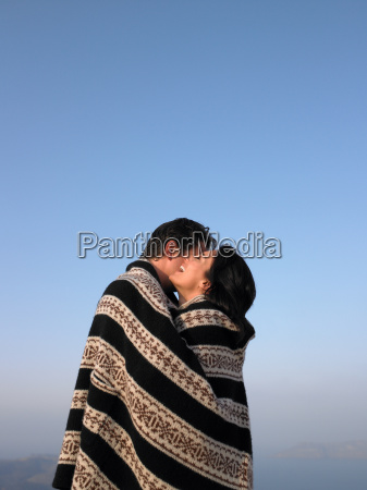 couple wrapped in a cover hugging