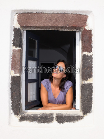 woman looking through window smiling