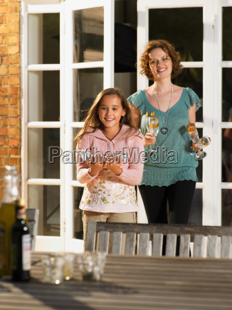 mother and daughter laying table outside
