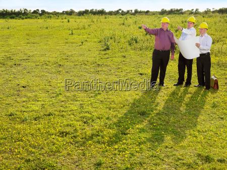 three surveyors on a field