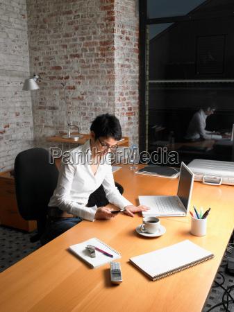 businesswoman sitting at desk on phone