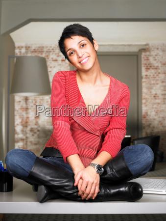 smiling businesswoman sitting on desk