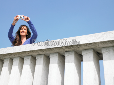 woman on balcony taking photograph