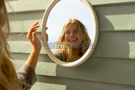 young woman looking in mirror outside