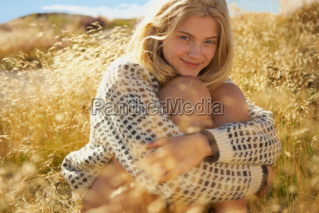 young woman sitting in long grass
