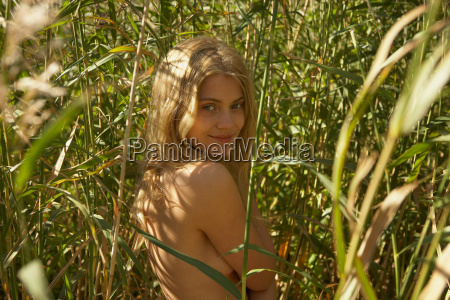 young woman nude in long grass