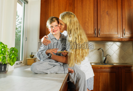 woman kissing young boy holding sandwich