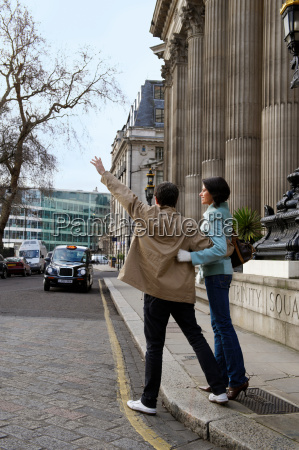 couple hailing london taxi