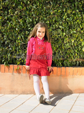 young girl against hedge