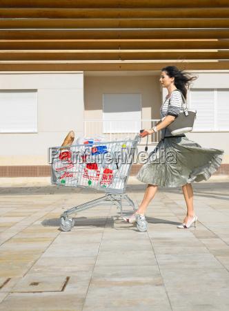woman pushing supermarket trolley