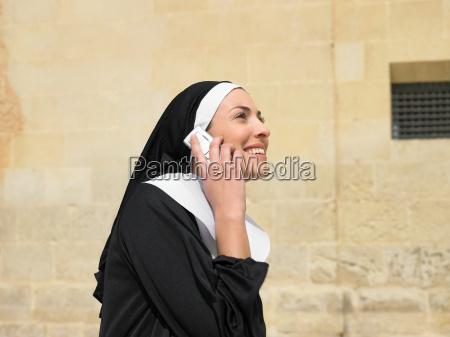 nun talking on mobile phone smiling