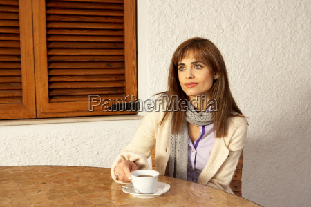 woman sitting at table holding coffee