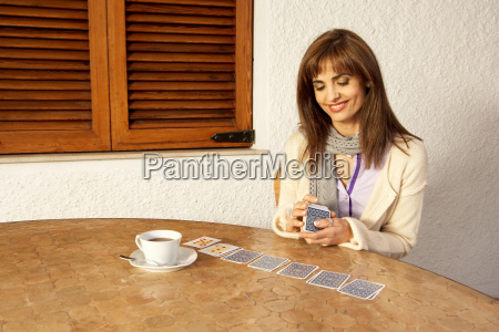 woman having coffee while playing cards