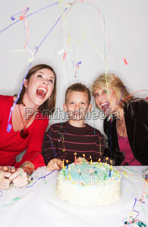 women and boy with birthday cake