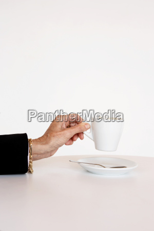 older womans hand holding cup