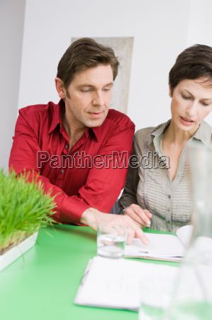 man and woman discussing some paper