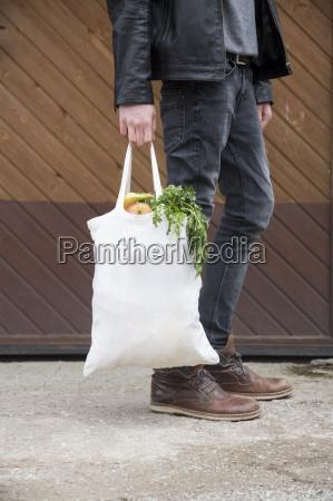 teenage boy traegt wiederverwendbare einkaufstaschen voller