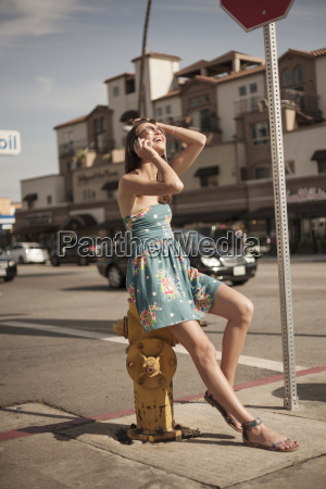 young woman sitting on fire hydrant