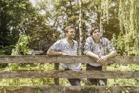 two male adult friends leaning against