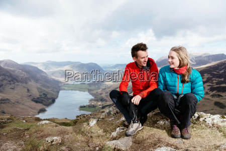 young couple sitting on hilltop honister