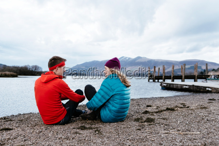 young couple hiking sitting by waters