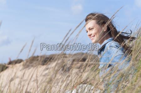 woman sitting on sand dunes on