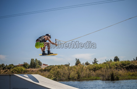 mid adult male wakeboarder jumping ramp