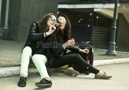 two young woman blowing bubbles on